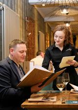 Pasta Di Piazza waitress helps a customer choose from the menu